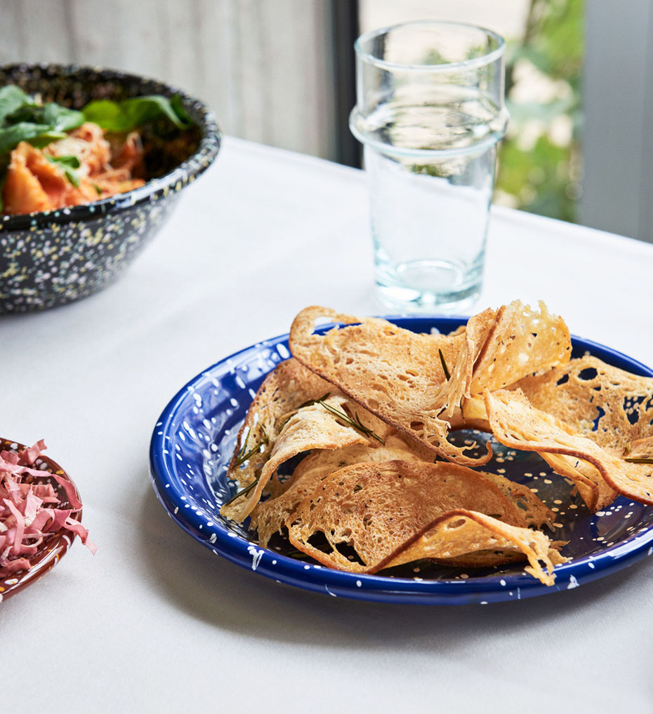 HAY Enamel Deep Plate Speckle Blue with bread chips